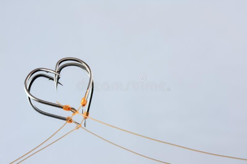 Heart Shape fishing hooks. On mirror royalty free stock images