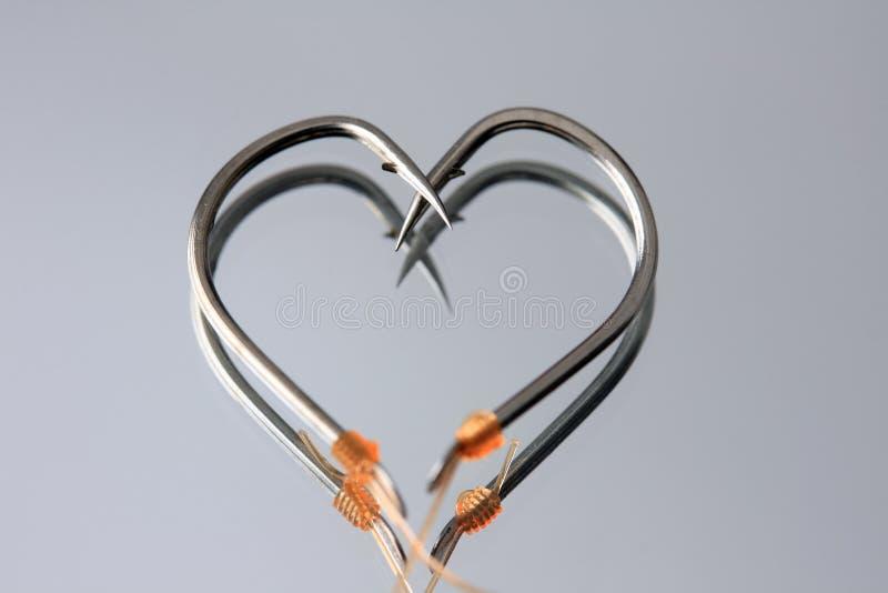 Heart Shape fishing hooks. On mirror stock photography