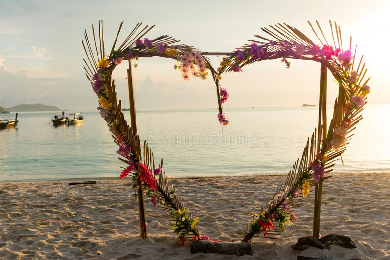 Heart shape flower arch on the beach. royalty free stock image