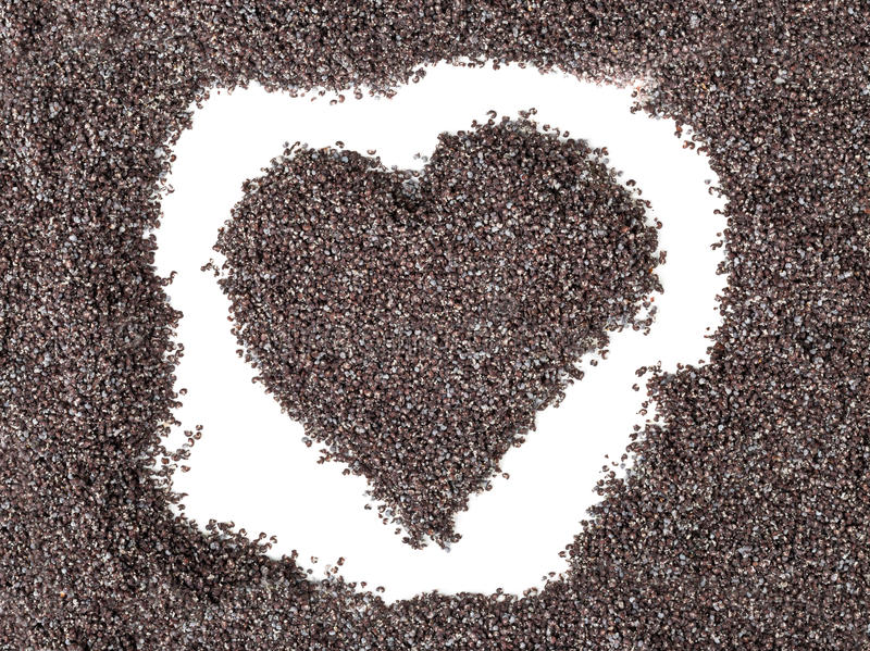 Heart shape formed by poppy seeds stock photography
