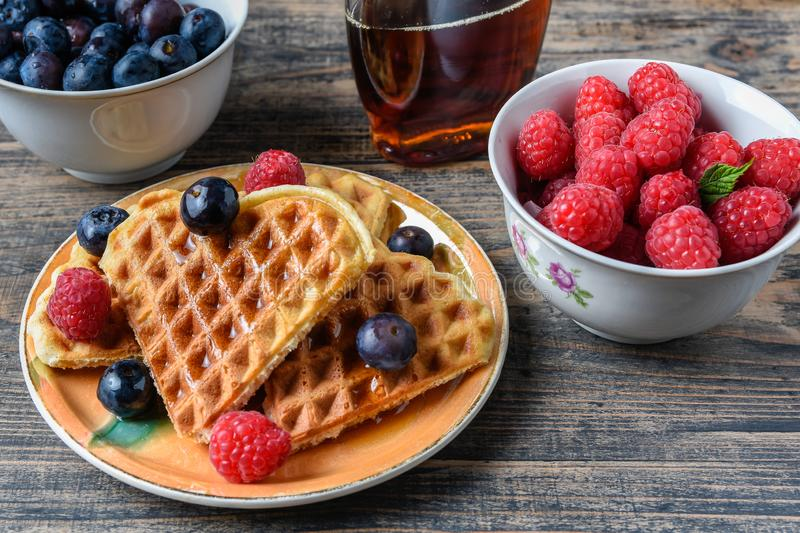 Heart shape gaufre with maple syrup and forest fruits on rustic wooden table stock images