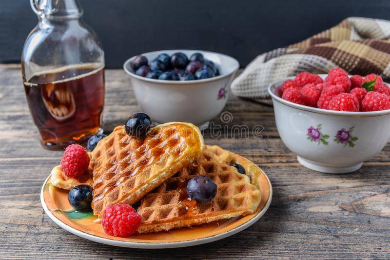 Heart shape gaufre with maple syrup and forest fruits on rustic wooden table stock image