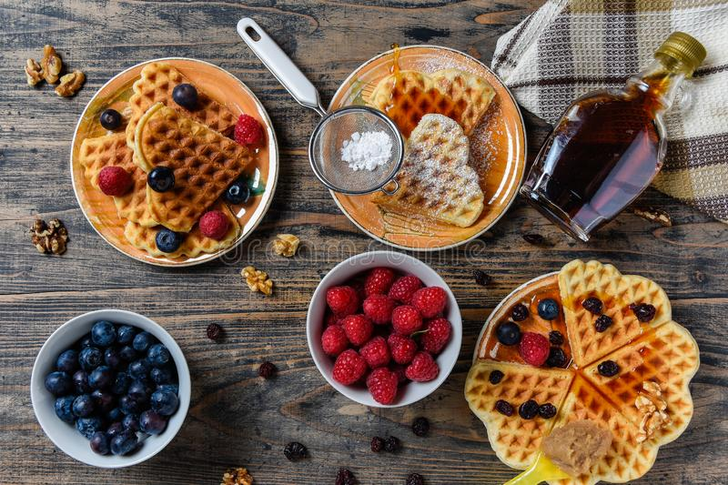 Heart shape gaufre with maple syrup and forest fruits on rustic wooden table royalty free stock photos