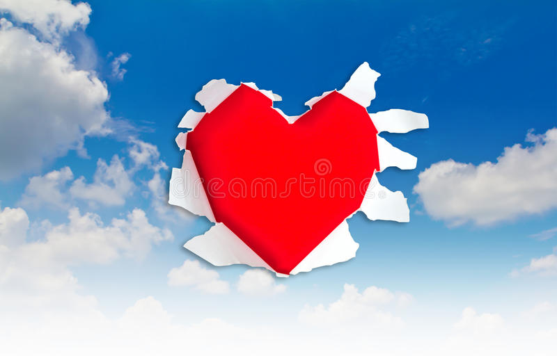 Heart shape hole through paper stock photo