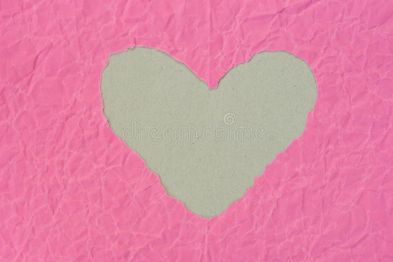 Heart shape hole on piece on pink paper royalty free stock photos