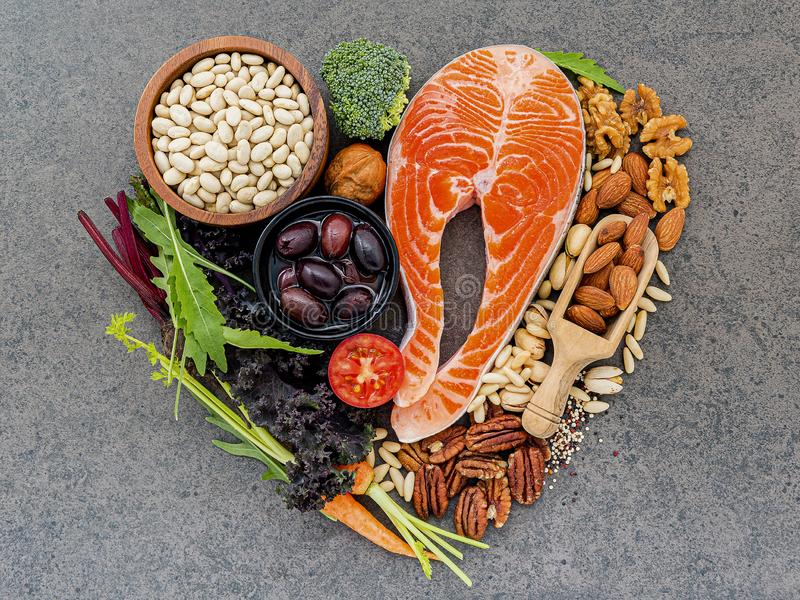 Heart shape of ingredients for healthy foods selection on dark stone background stock photo