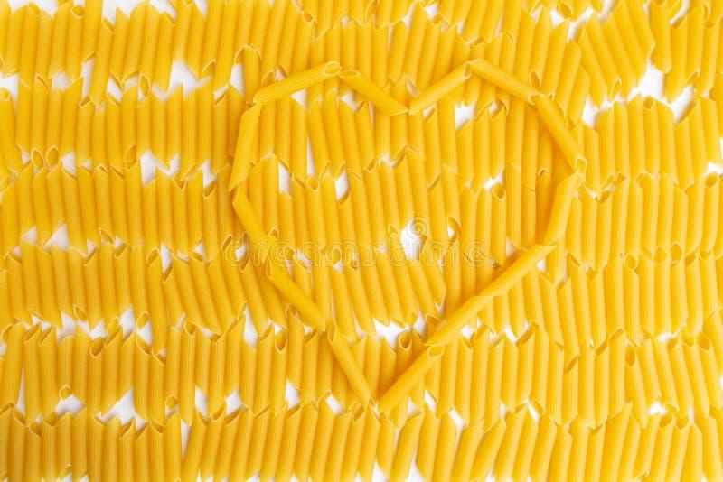 Heart shape of Italian Penne Rigate Macaroni Pasta on background royalty free stock image