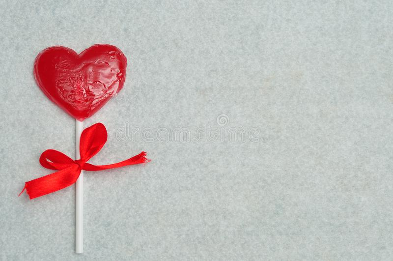 A heart shape lollipop with a red ribbon tied to the stick part stock photos