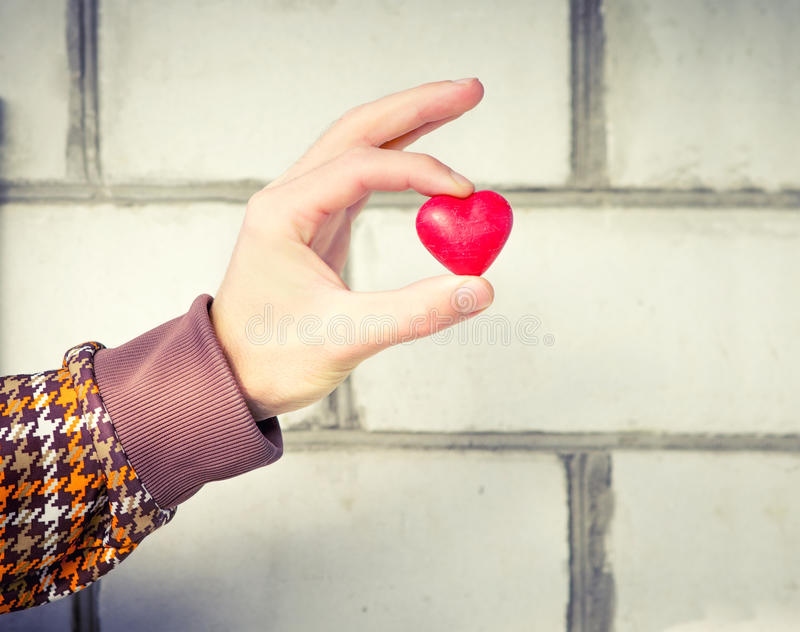 Heart shape love symbol in man hand Valentines Day. Romantic greeting with brick wall on background people relationship concept winter holiday stock photography