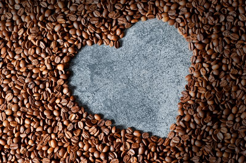 Heart shape made from brown and black roasted coffee beans or grains background royalty free stock images