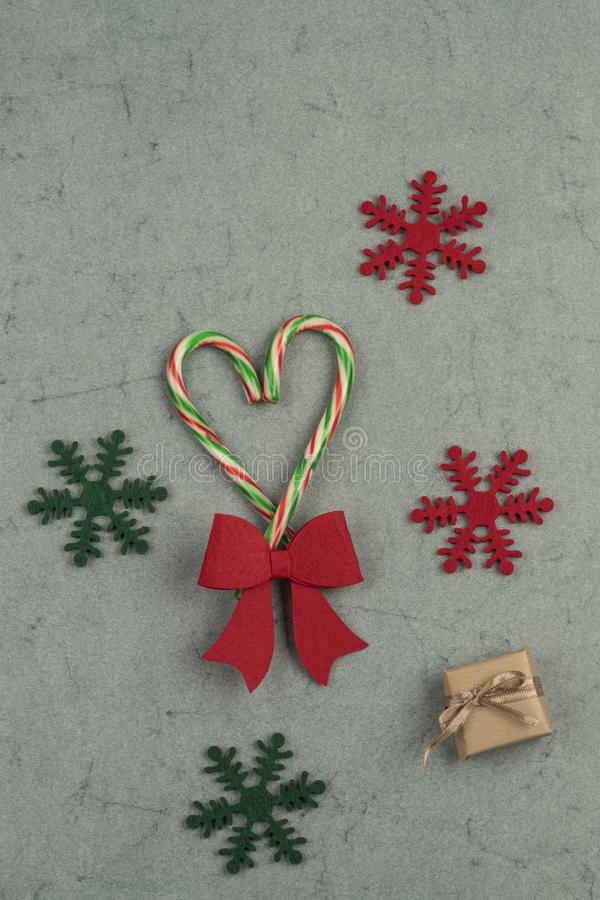 Heart shape made with candy canes on a green background for new year stock photo