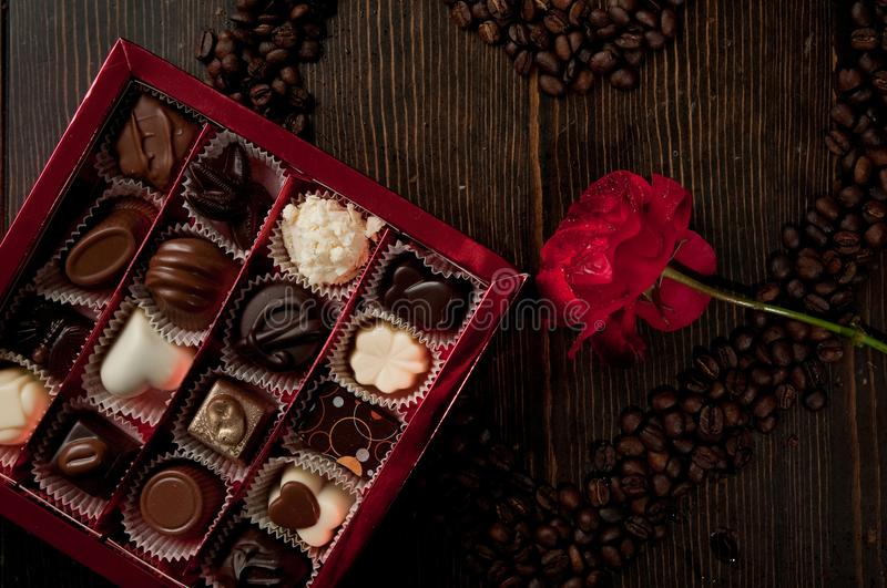 heart shape made from coffee beans and a box of chocolate pralines completed with red romantic rose on a table royalty free stock photo