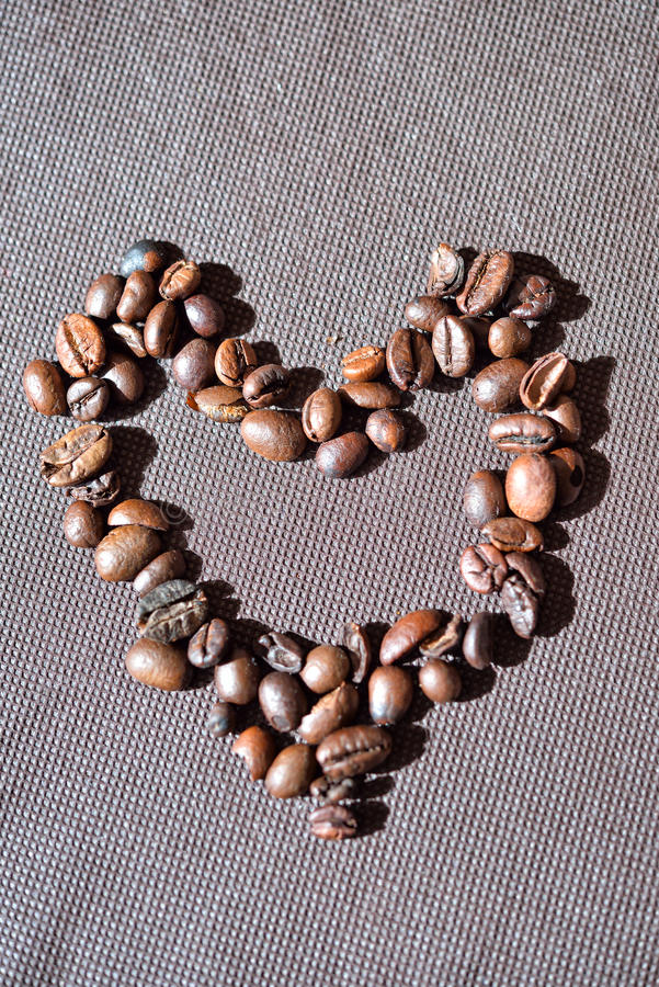 Heart shape made from coffee beans on brown background royalty free stock image