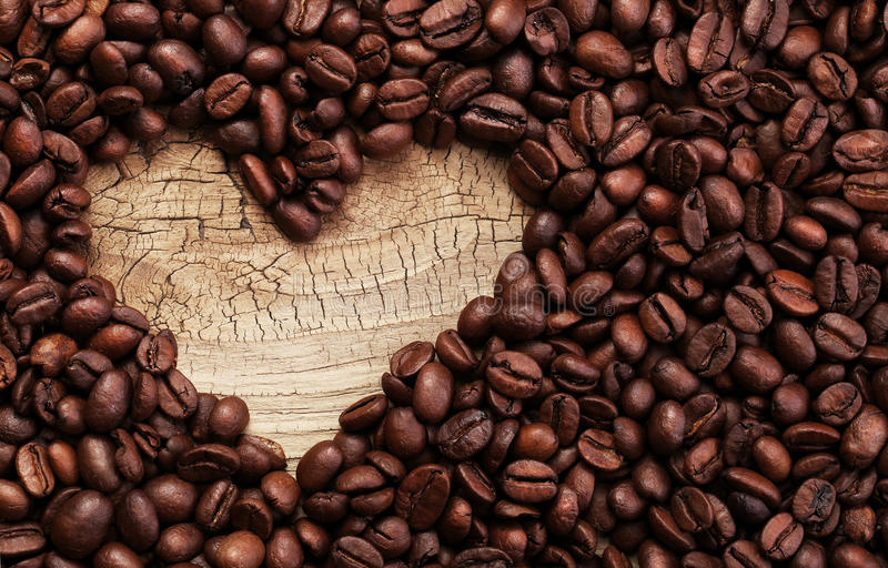 Heart shape made from coffee beans on wooden surface stock image
