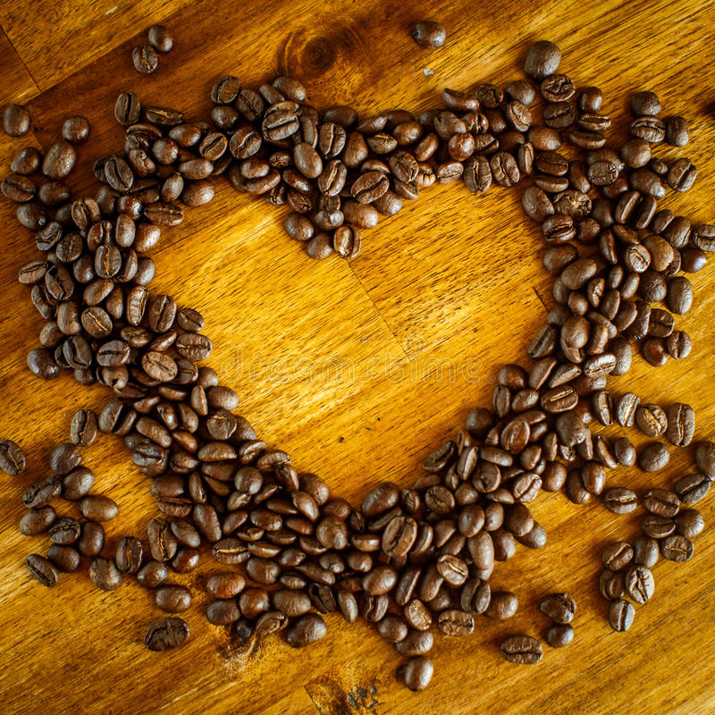 Heart shape made from coffee beans on wooden surface. royalty free stock image