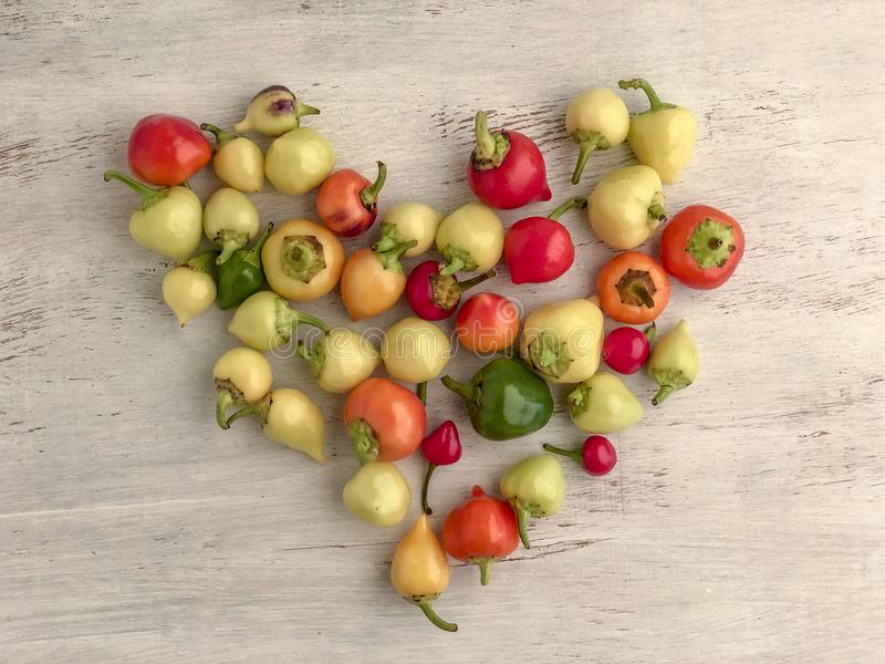 Heart shape made with colorful fresh peppers on wooden table royalty free stock photos