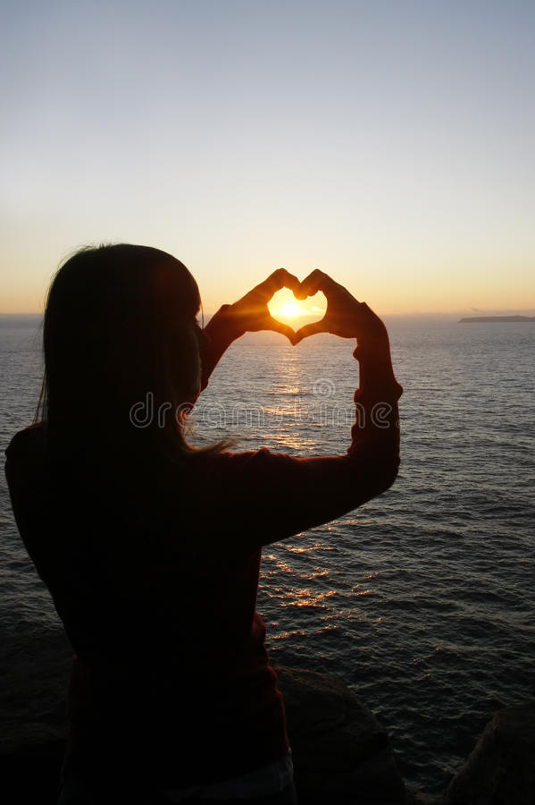 Heart shape made with a girl hands royalty free stock photography