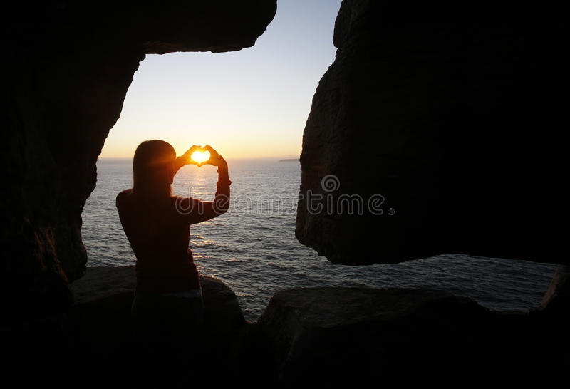 Heart shape made with a girl hands royalty free stock image