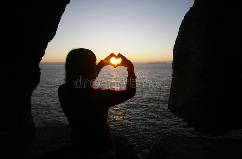 Heart shape made with a girl hands stock photos