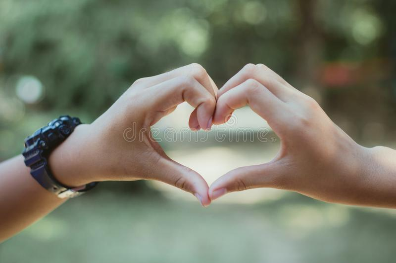 Heart shape made with hands of female student, Love symbol concept. royalty free stock images