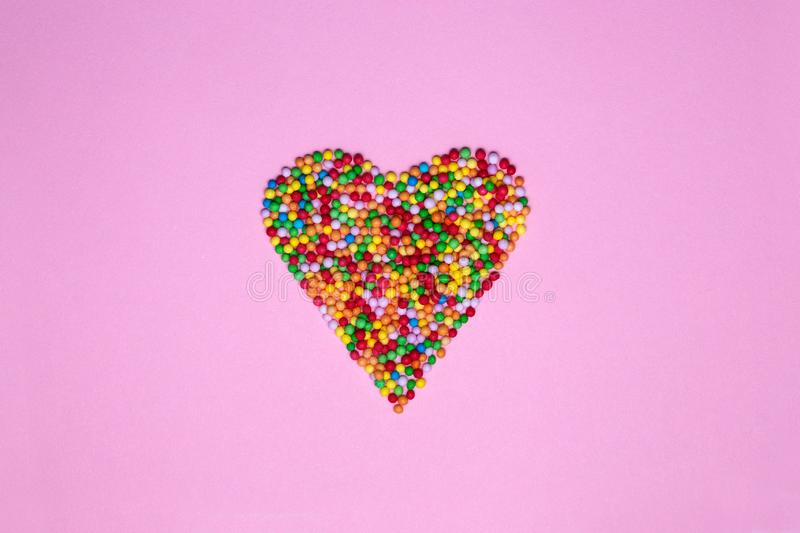 Heart shape made of hundreds and thousands on a pink background royalty free stock photography