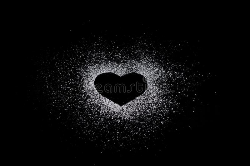 Heart shape made of icing sugar on total black background with c royalty free stock photo