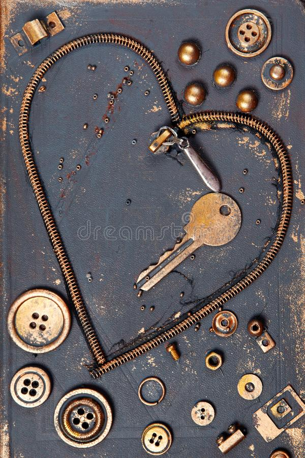 Heart shape made of metal zipper, key, buttons and other garbage. stock photo