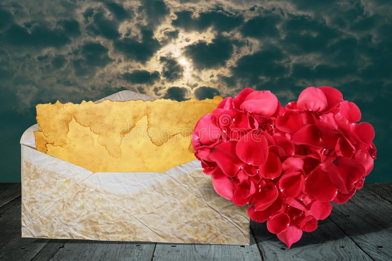 Heart shape made out of rose petals with old letter on wooden deck table royalty free stock image