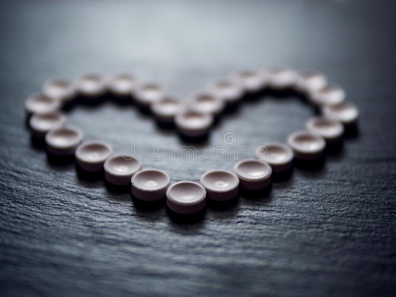 Heart shape made of pills, concept health care, medicine. Moody lighting. Selective focus royalty free stock images
