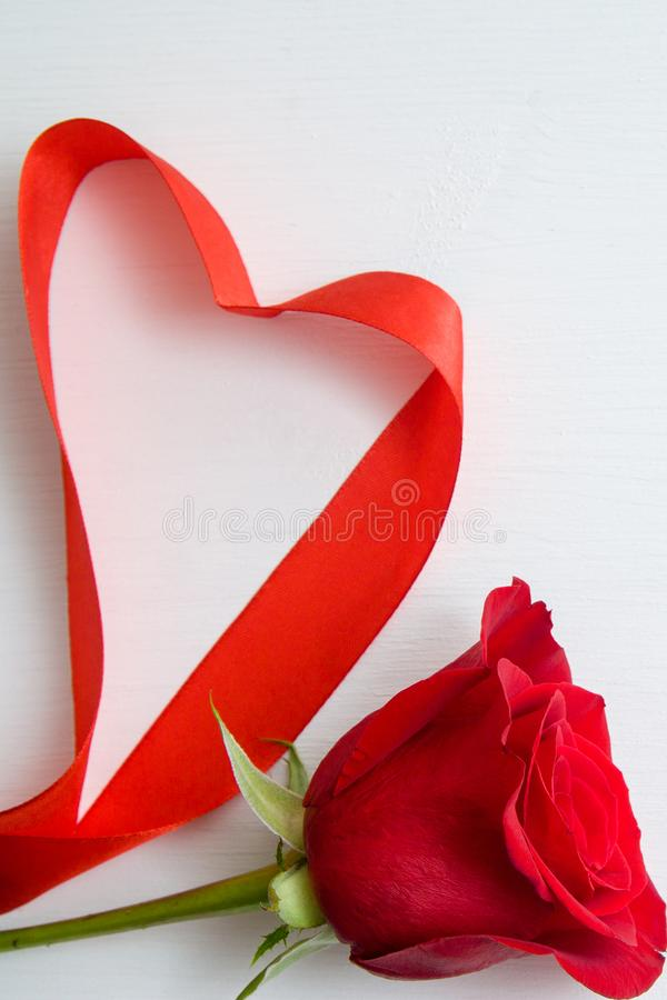 Heart shape made Of red ribbon with red rose on white wooden Background. copy space - Valentines and 8 March Mother Womens Day stock photo
