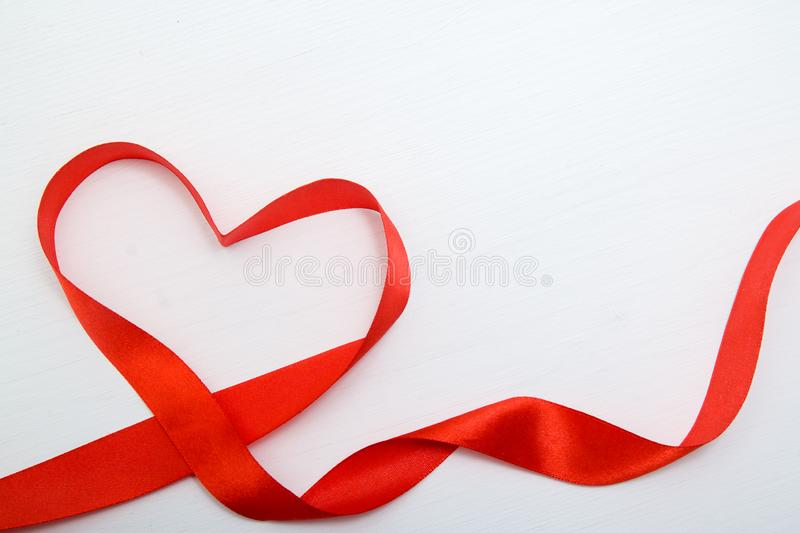 Heart shape made of red ribbon on white wooden Background. copy space - Valentines and 8 March Mother Women& x27;s Day concept stock image
