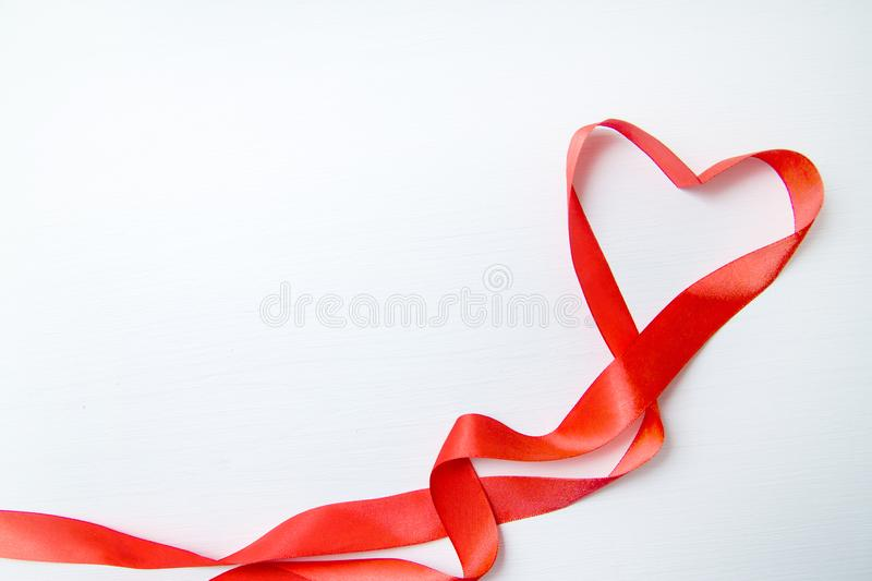 Heart shape made of red ribbon on white wooden Background. copy space - Valentines and 8 March Mother Women& x27;s Day concept royalty free stock image