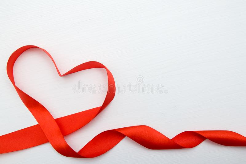 Heart shape made of red ribbon on white wooden Background. copy space - Valentines and 8 March Mother Women Day concept stock images