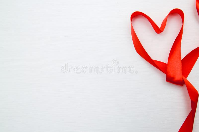 Heart shape made of red ribbon on white wooden Background. copy space - Valentines and 8 March Mother Womens Day concept royalty free stock photos
