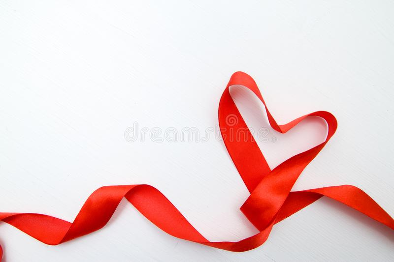 Heart shape made of red ribbon on white wooden Background. copy space - Valentines and 8 March Mother Women& x27;s Day concept stock images