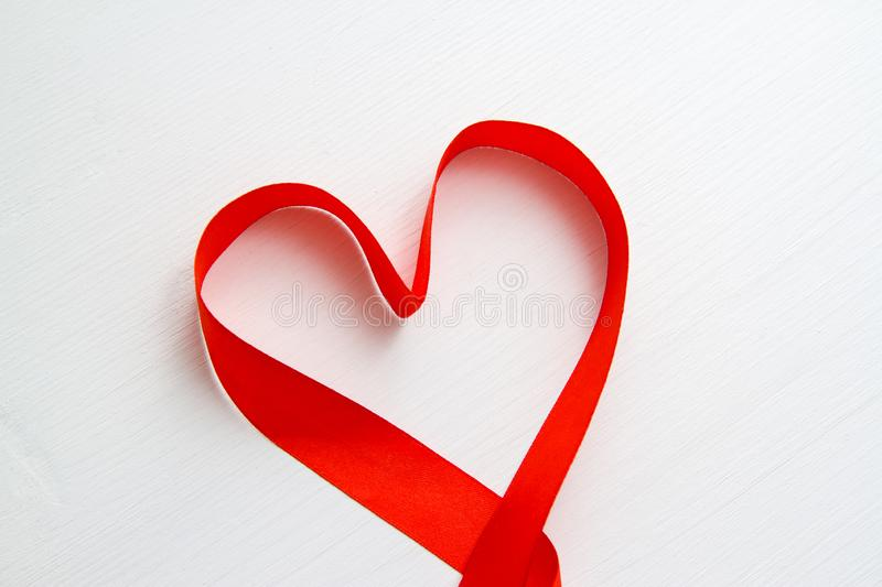 Heart shape made of red ribbon on white wooden Background. copy space - Valentines and 8 March Mother Women`s Day concept royalty free stock images