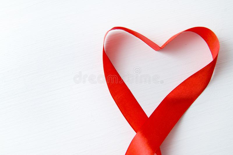 Heart shape made of red ribbon on white wooden Background. copy space - Valentines and 8 March Mother Women`s Day concept stock photography