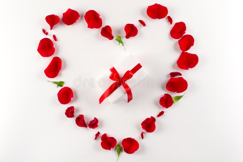 Heart shape made of red rose petals and white gift box with red ribbon on white background. Top view, copy space stock photo