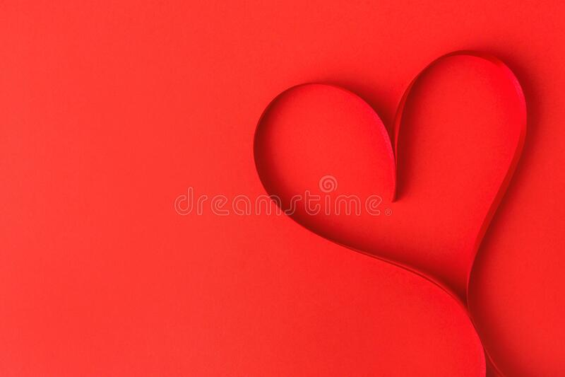 Heart shape made from ribbon on red stock photo