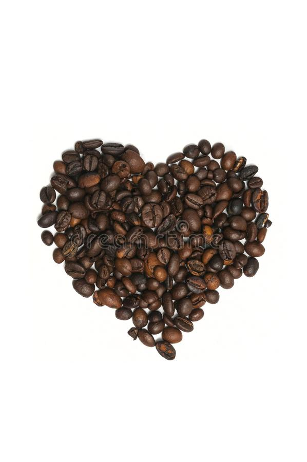Heart shape made with some fresh roasted coffee beans isolated on white background royalty free stock images