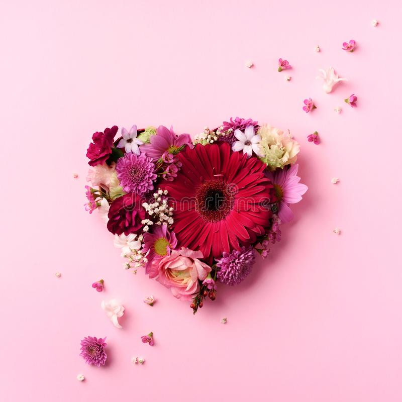 Heart shape made of spring flowers on pink punchy pastel background. Top view, flat lay. Summer concept. Valentine's day. Creativ stock photo