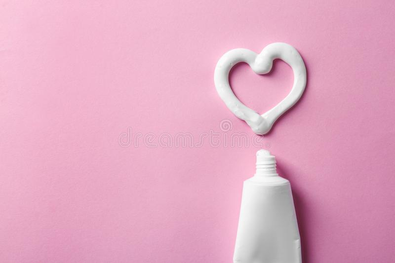 Heart shape made of toothpaste near tube and space for text on color background stock photo