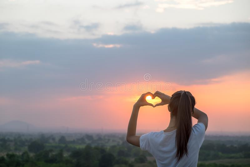 Heart-shape for the nature. Female making symbol for loving the season stock photo