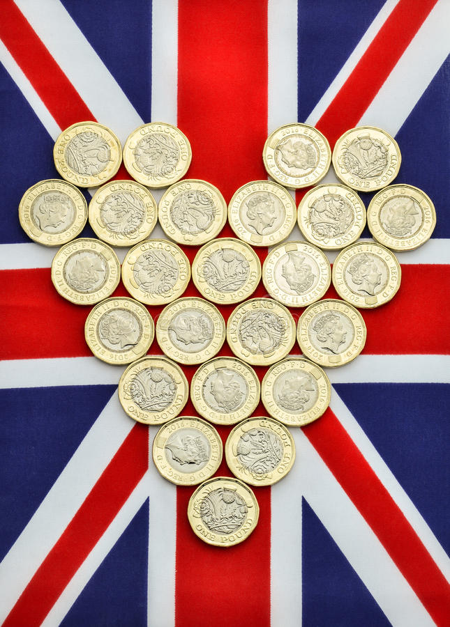 Heart shape of new pound coins on British flag. New British pound coins in the shape of a heart on a Union Jack flag. This one pound coin was introduced in stock photo