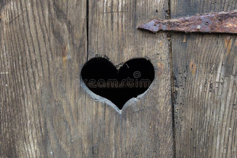 Heart shape on an old door stock image