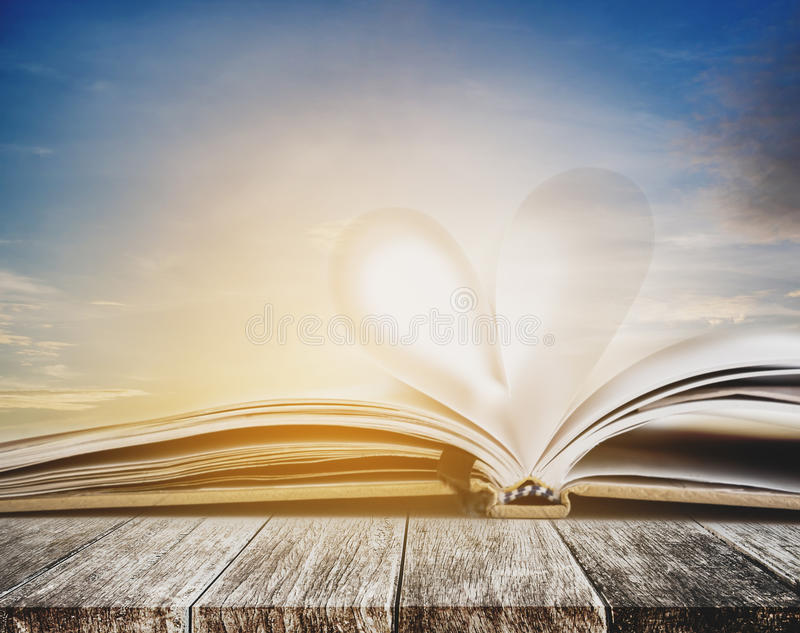 Heart shape on opened notebook page, on wooden table, with sunset sky in summer background, vintage colors toned stock photos