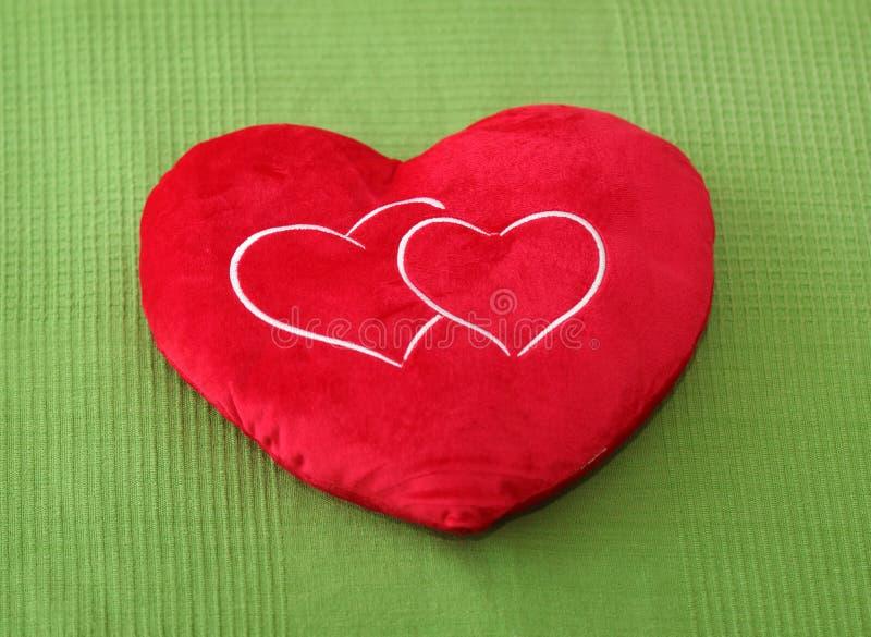 Heart shape pillow. On green background stock photos