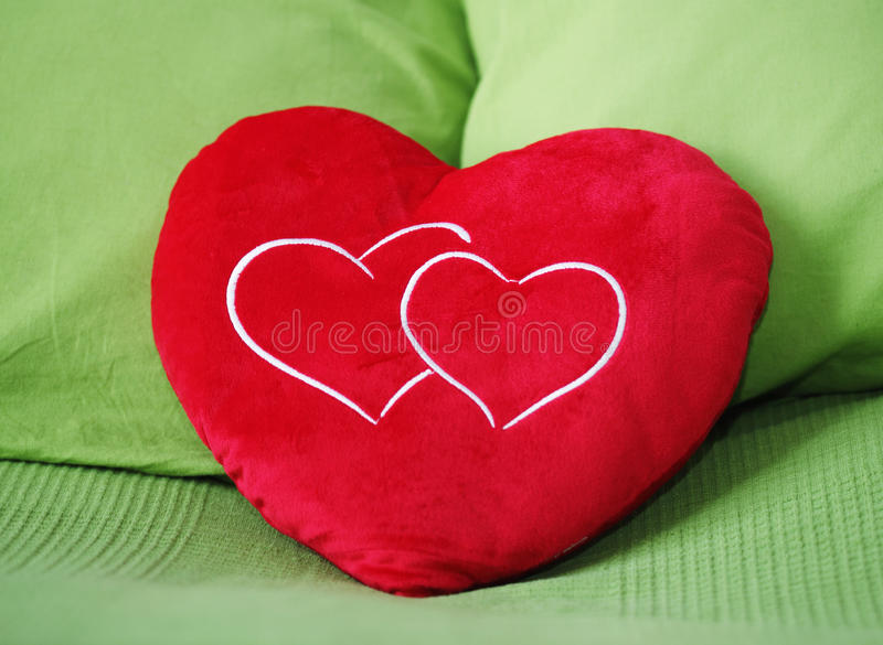Heart shape pillow. On green background royalty free stock images