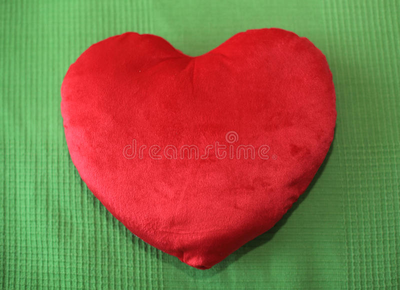 Heart shape pillow. On green background royalty free stock photo