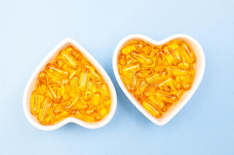 Heart-shape plate with fish oil capsules omega 3, healthy product   and   supplement  concept close up, royalty free stock photography